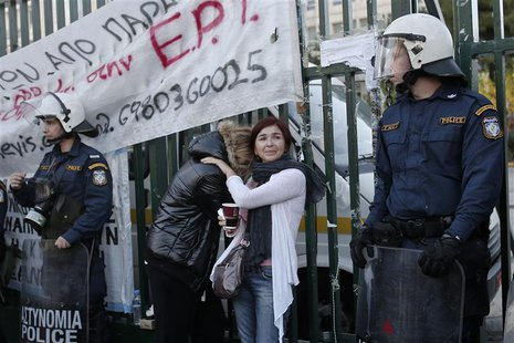 Former employees of the Greek state television ERT comfort each other outside its headquarters at Agia Paraskevi suburb north of Athens Nove