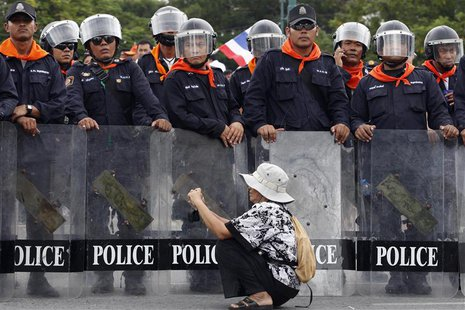 A woman takes pictures in front of a line of policemen blocking protesters against an amnesty bill, on the main road near the government and