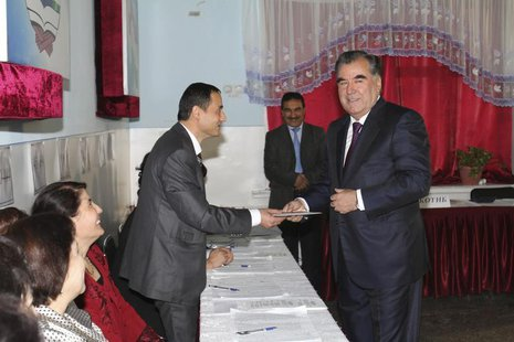 Tajikistan's President Imomali Rakhmon (R) receives his ballot from an electoral official during the presidential election in Dushanbe, in t