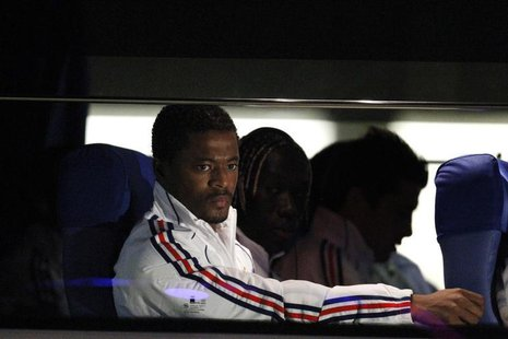 France's national soccer player Patrice Evra (L) sits in the team bus after arriving at the airport in Bloemfontein June 21, 2010. FREUTERS/