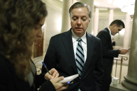 U.S. Senator Lindsey Graham (C) talks to a reporter as he arrives for a Republican Senate caucus meeting at the U.S. Capitol in Washington,