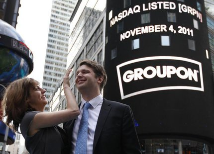 Groupon Chief Executive Andrew Mason poses with his newly married wife, pop musician Jenny Gillespie, outside the Nasdaq Market following hi