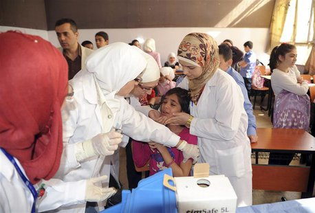 Syrian health workers administer polio vaccination to a girl at a school in Damascus, in this file photo taken by Syria's national news agen