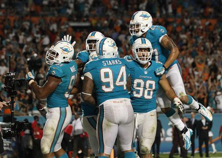 Miami Gardens, FL, USA; Miami Dolphins defensive end Cameron Wake (91) celebrates with defensive tackle Randy Starks (94) defensive tackle J
