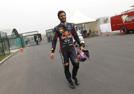Red Bull Formula One driver Mark Webber of Australia returns to the garage area after retiring from the race during the Indian F1 Grand Prix