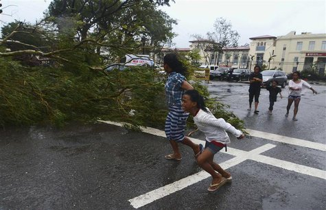 Residents rush to safety past a fallen tree during strong winds brought by Typhoon Haiyan that hit Cebu city, central Philippines November 8