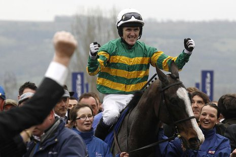 Tony McCoy on Synchronised celebrates as he enters the unsaddling enclosure after winning The Gold Cup at the Cheltenham Festival horse raci