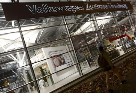 A woman passes a shop-window of German carmaker Volkswagen at a VW dealership in Hamburg, October 28, 2013. REUTERS/Fabian Bimmer