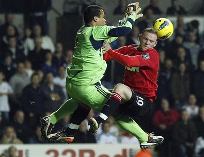 Swansea City's Michel Vorm (L) challenges Manchester United's Wayne Rooney (R) during their English Premier League soccer match at the Liber