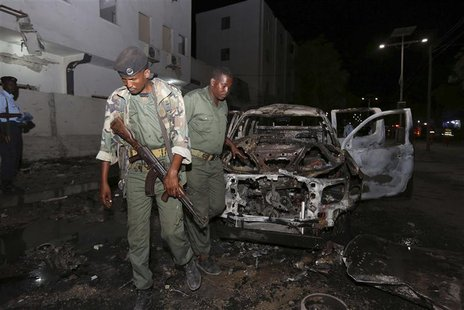 Somali policemen inspect the scene of an explosion outside the Maka Al-Mukarama hotel in Somalia's capital Mogadishu, November 8, 2013. REUT