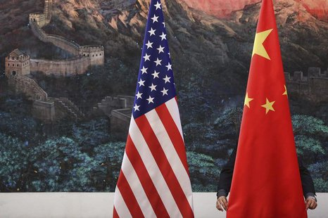 A Chinese man adjusts a China flag before a news conference attended by Chinese Foreign Minister Yang Jiechi and U.S. Secretary of State Hil