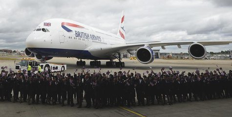 Workers welcome British Airways' new Airbus A380 as it taxis to a hanger after landing at Heathrow airport in London July 4, 2013. REUTERS/P