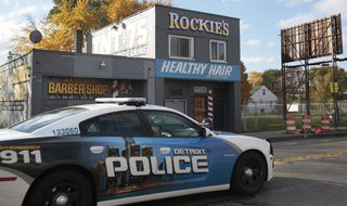 A Detroit Police car drives past a barbershop on Seven Mile Road, where the night before a shooting occurred, in Detroit, Michigan November