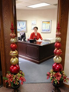 MaryKay Hazelbaker models the holiday pillars in her office doorway at Century Bank and Trust.
