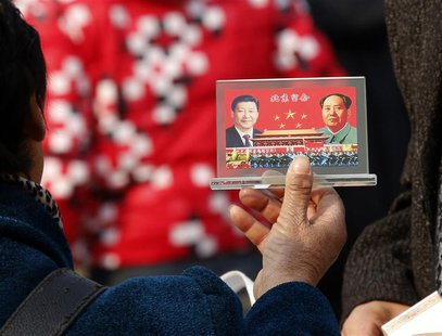A street vendor displays a souvenir with pictures of Chinese President Xi Jinping (L) and the late Chinese Chairman Mao Zedong to visitors a
