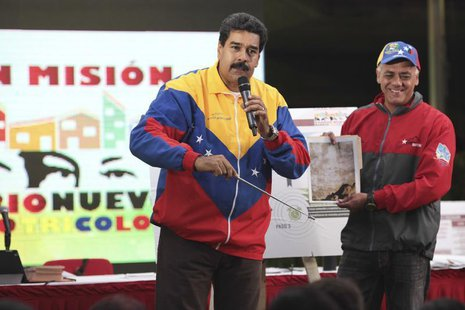 Venezuela's President Nicolas Maduro (L) shows a picture of a metro tunnel wall with an image which he says is the face of late President Hu