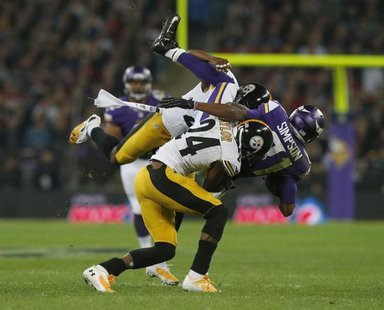 Minnesota Vikings wide receiver Jerome Simpson (R) is brought down by Pittsburgh Steelers cornerback Ike Taylor and another defender in the