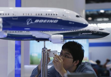 A visitor takes a picture of miniature Boeing passenger aircraft on display at Aviation Expo China 2013 in Beijing September 25, 2013. REUTE