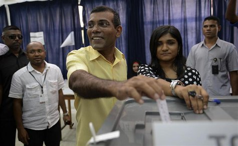 Maldivian Democratic Party (MDP) presidential candidate Mohamed Nasheed, who was ousted as president in 2012 (C), casts his vote at a pollin