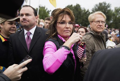 "Senator Mike Lee (L)(R-UT) watches as Former Alaska Governor Sarah Palin hands out American Flags to protesters during the ""Million Vet Marc"