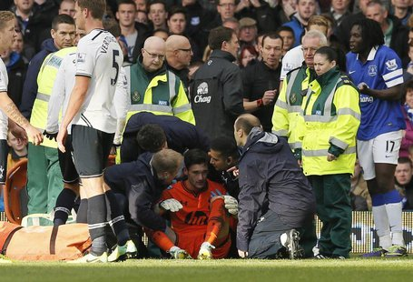 Tottenham Hotspur's goalkeeper Hugo Lloris (C) is attended to by medical staff after being involved in a collision with Everton's Romalu Luk