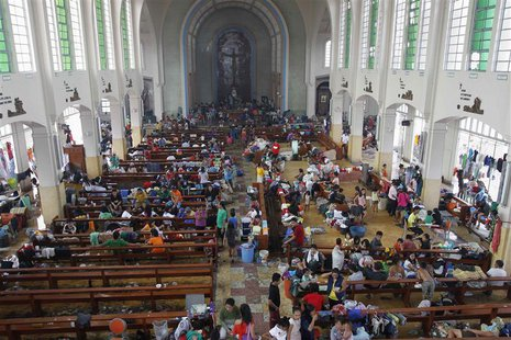 Residents seek refuge inside a Catholic church which has been converted into an evacuation center after super Typhoon Haiyan battered Taclob