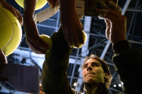 Rafael Nadal of Spain signs autographs after defeating Roger Federer of Switzerland in their men's singles semi-final tennis match at the AT
