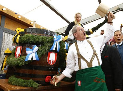 Munich Mayor Christian Ude taps the first barrel of beer during the opening ceremony for the 180th Oktoberfest in Munich September 21, 2013.