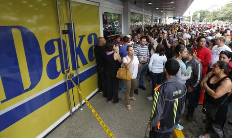Shoppers crowd outside a Daka store as they wait to shop for electronic goods in Caracas November 9, 2013. REUTERS/Carlos Garcia Rawlins