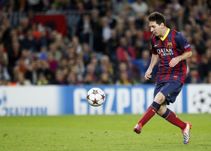 Barcelona's Lionel Messi kicks the ball to score his second goal against AC Milan during their Champions League soccer match at Nou Camp sta