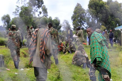 Congolese M23 rebels walk inside an enclosure after surrendering to Uganda's government at Rugwerero village in Kisoro district, 489km (293