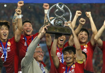 China's Guangzhou Evergrande coach Marcello Lippi (front L) and player Zheng Zhi (front R) hold up the trophy after winning their final matc