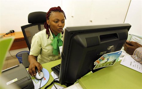 An employee registers a customer for a mobile money transfer, known as M-Pesa, inside the Safaricom mobile phone care centre in the central