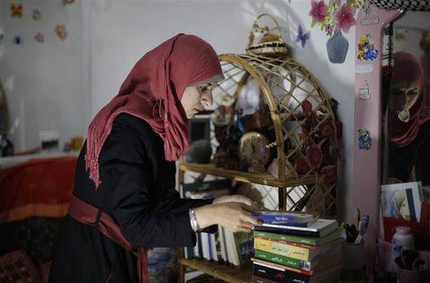 Isra Al-Modallal, a spokeswoman of the Hamas government in Gaza, prepares herself before heading to the office, at her house in Rafah refuge