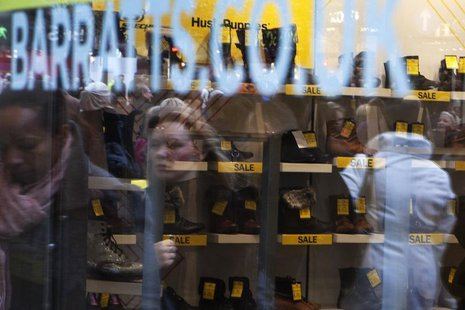 Passers-by are reflected in the display window of Barratts shoe shop on Oxford Street in central London, December 8, 2011. REUTERS/Finbarr O