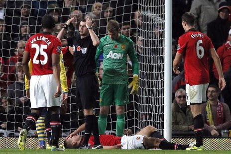 Referee Michael Oliver signals on the medics as Manchester United's Nemanja Vidic lays injured during their English Premier League soccer ma