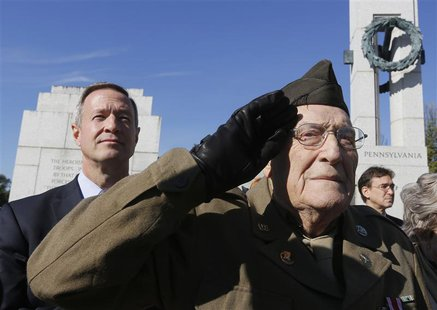 World War Two veteran Anthony Gizzi, 90, of Haverstraw, New York, salutes next to Maryland Governor Martin O'Malley (L) while honoring his f