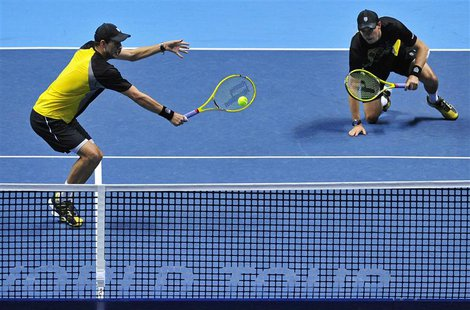 Bob Bryan of the U.S. slips as his brother Mike Bryan plays a shot during their men's doubles final tennis match against David Marrero of Sp