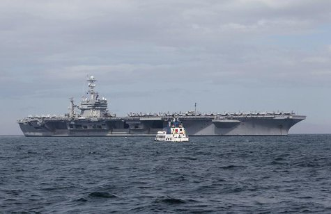 A tugboat approaches the U.S. Navy aircraft carrier George Washington docked after its arrival at a Manila bay October 24, 2012. REUTERS/Rom