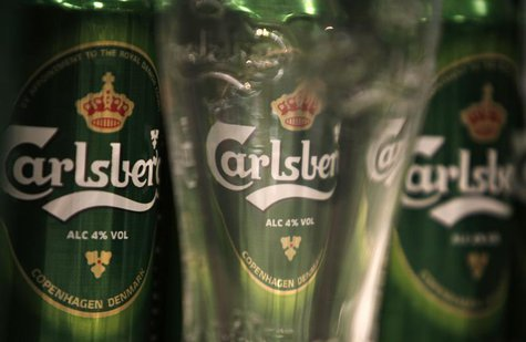 Cans of Carlsberg beer are seen through a branded pint glass before a news conference in London January 25, 2008. REUTERS/Stephen Hird