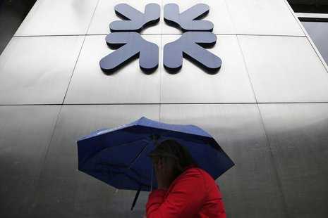 A woman shelters under an umbrella as she walks past a branch of the Royal Bank of Scotland in the City of London September 17, 2013. REUTER
