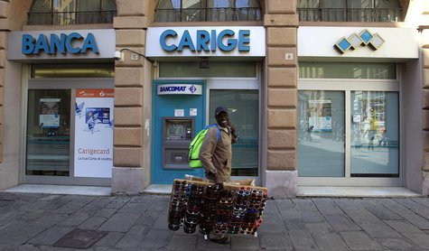 A street vendor walks in front of Carige bank in Genoa May 14, 2013. REUTERS/Alessandro Garofalo