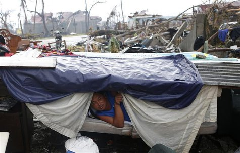 A typhoon victim looks out from a makeshift shelter along a road in Palo, Leyte province in central Philippines, which was battered by Typho