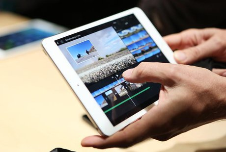 A member of the media holds the new iPad mini with Retnia display during an Apple event in San Francisco, California October 22, 2013. REUTE