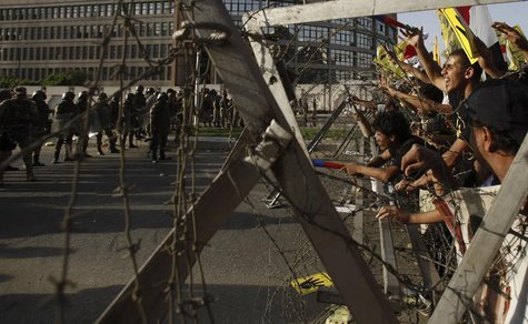 Members of the Muslim Brotherhood and supporters of ousted Egyptian President Mohamed Mursi shout slogans next to barbed wire as army soldie