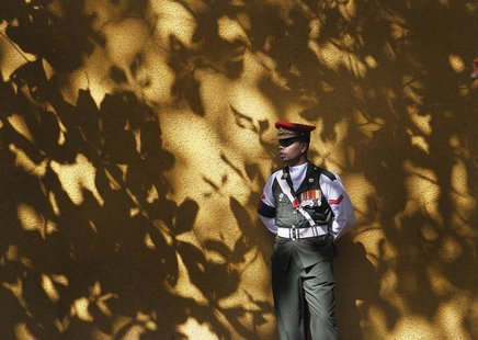 A soldier on duty looks on as he stands guard at an entrance at the World World II war memorial during an event marking Remembrance Day, als