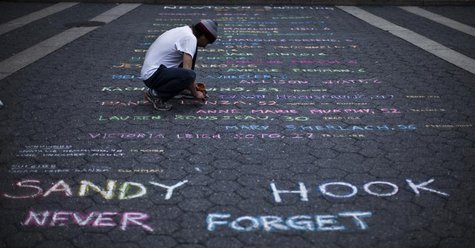 Street artist Mark Panzarino, 41, prepares a memorial as he writes the names of the Sandy Hook Elementary School victims during the six-mont