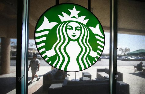 A Starbucks logo hangs on a window at a newly designed Starbucks coffee shop in Fountain Valley, California August 22, 2013. REUTERS/Mike Bl