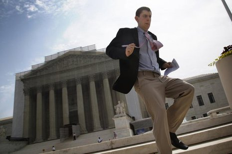 A television news producer sprints down the steps from the U.S. Supreme Court building with their printed rulings in cases heard earlier thi
