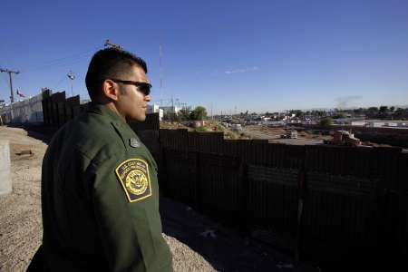 A Border Patrol Agent looks over to Mexico from the US side of the international border near Calexico, California, adjacent to the Mexican border town of Mexicali, November 3, 2009. REUTERS/Lucy Nicholson